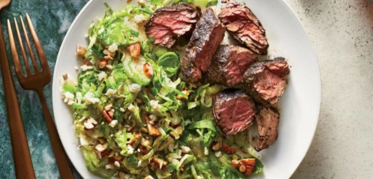 Brussels Sprouts Salad with Coffee-Rubbed Steak on a white plate