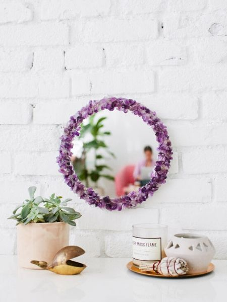 mirror hanging on a wall with purple flower around it