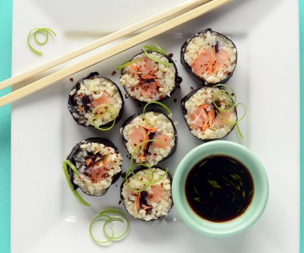 Paleo Sushi Salmon Roll With Cauliflower Rice on a plate with chopstick