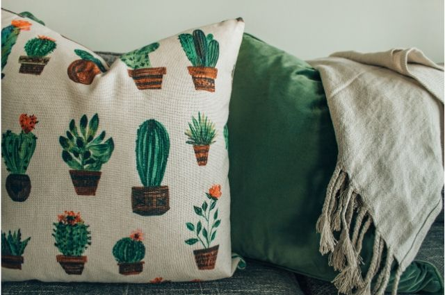 Two cushions with green and grey colors and a grey linen on top of the green cushion