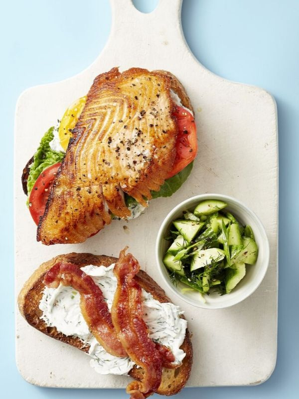 Cutting Board with Salmon, Bacon, Lettuce, Tomatoes and Pickles on Top