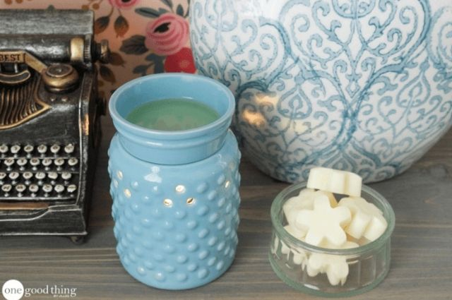 Blue candle aromatherapy furnace with bowl of wax melts beside it