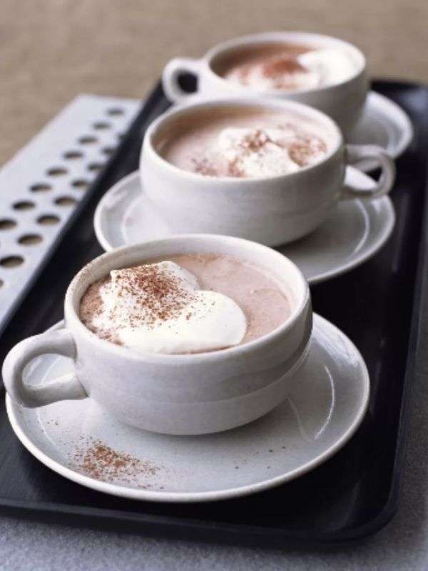 3 row of white mugs filled with hot chocolate and whipped cream