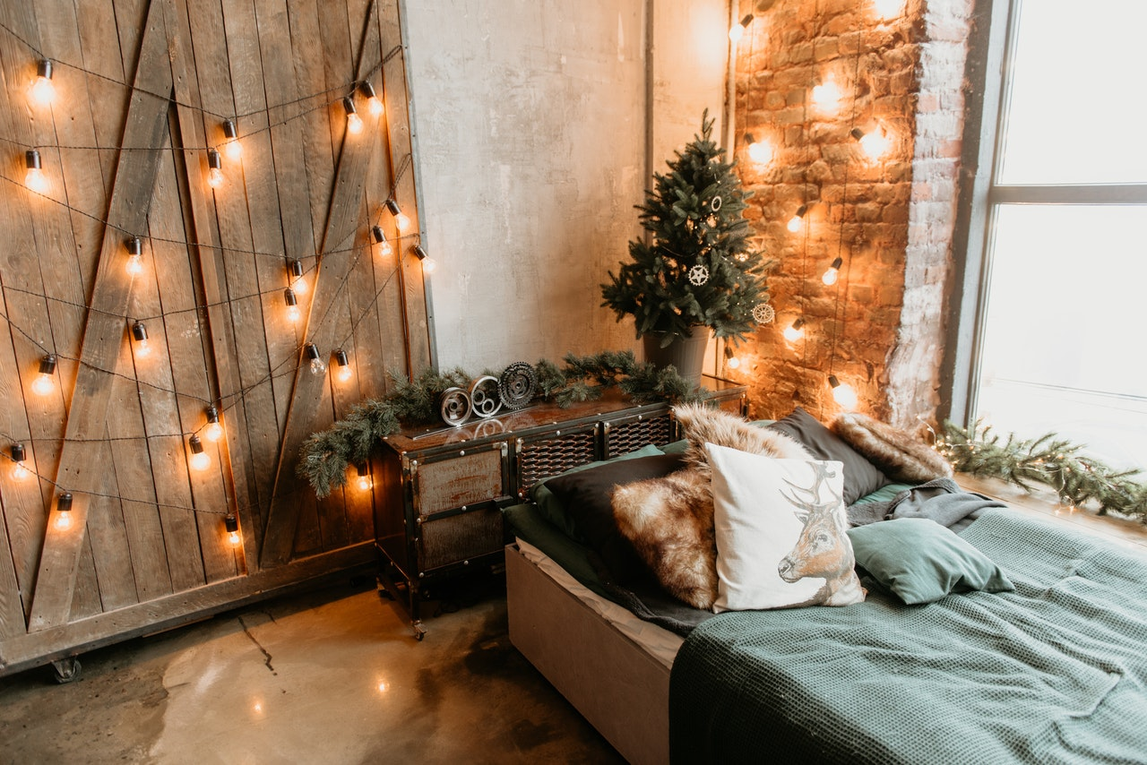 A room filled with lamps decoration on a wall, small pine tree decoration and a bed