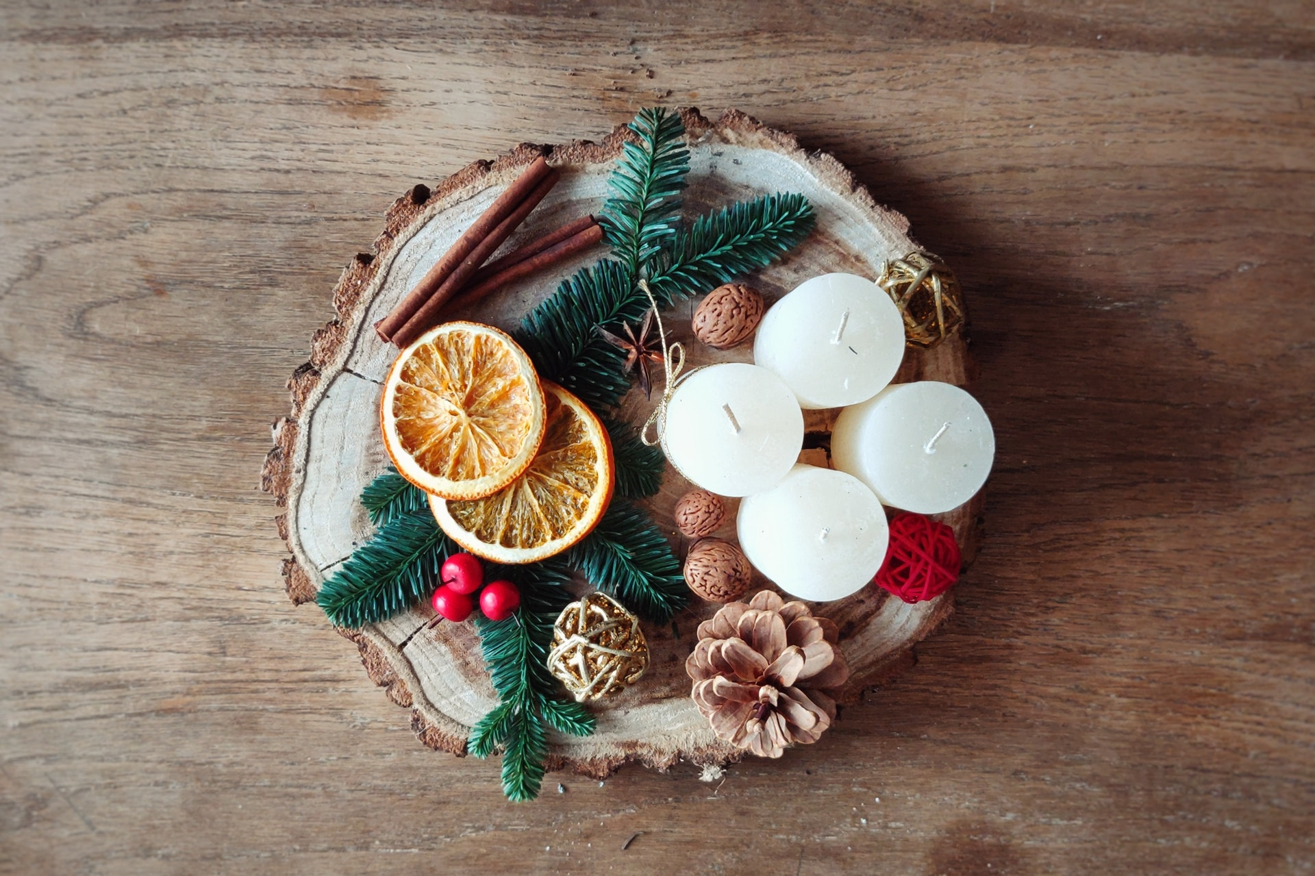 candles, orange skin and pines on top of wood plate
