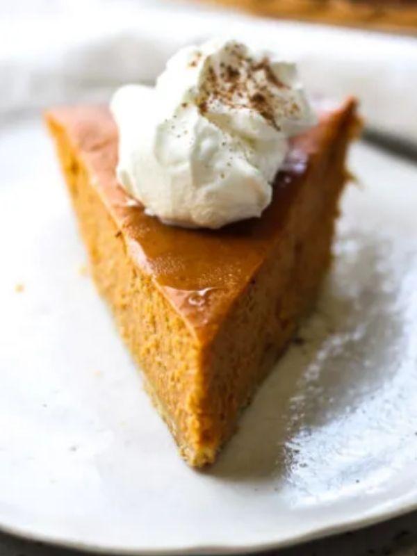 A slice of Pumpkin pie with cream over it