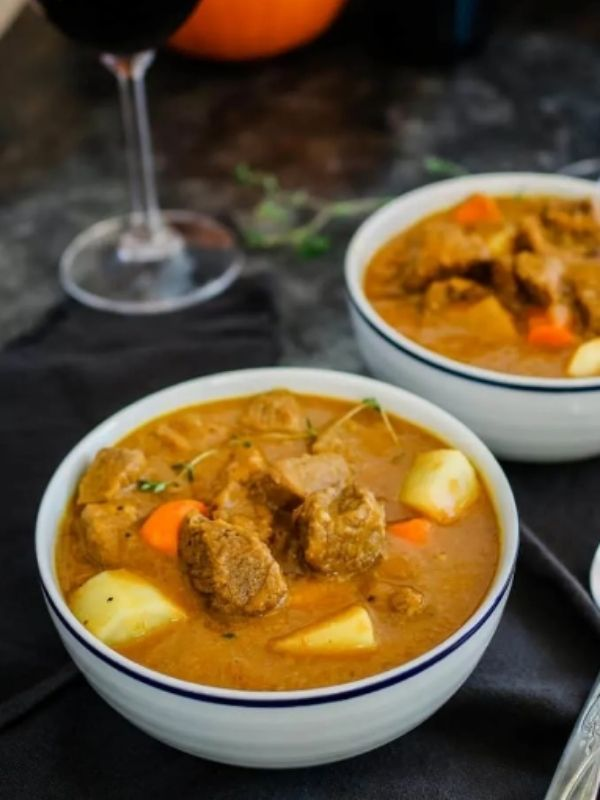 Two bowls of pumpkin beef stew with a glass of wine behind it