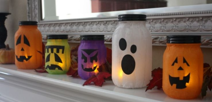 Five different shapes and colors of Jack O'Lanterns mason jar on a mantel.