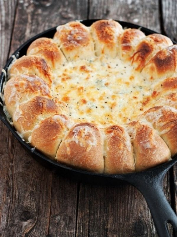 Bread and artichoke dip on a black skillet.