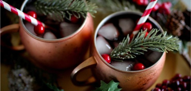Two copper cups of cranberries sangria with a straw and rosemary in each cup.