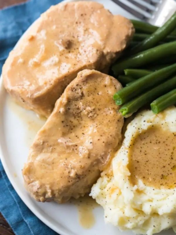 A plate filled with veggies, pork chops, mashed potatoes, and gravy spread over them.